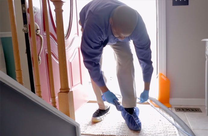 Man wearing protective shoe covers while entering the home